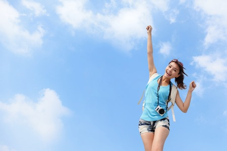 Happy woman traveler raising arm with sky background Фото со стока