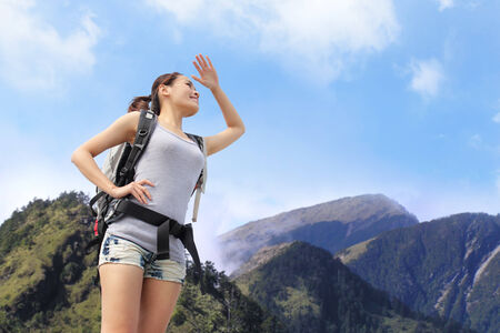 happy woman mountain hiker with backpack and looking to sky on the top of mountains. asian photo