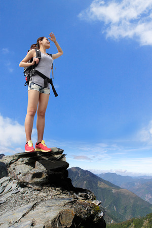 happy woman mountain hiker with backpack and looking to sky on the tpo of mountains. asian photo