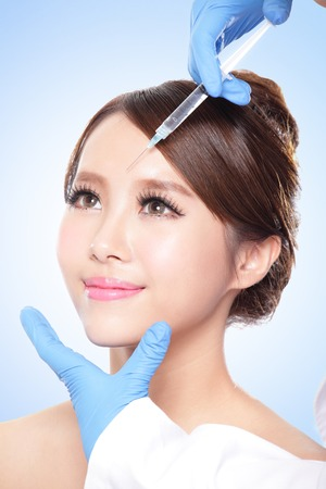 injection woman: Close up of cosmetic injection to the pretty woman face. Isolated on blue background, asian Stock Photo