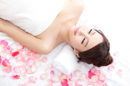 enjoy space: Beautiful young woman enjoy massage at spa with roses, she is very relaxed, asian beauty Stock Photo