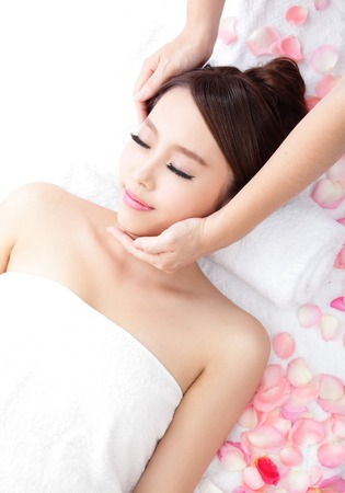 Beautiful young woman enjoy face massage at spa with roses, asian beauty photo
