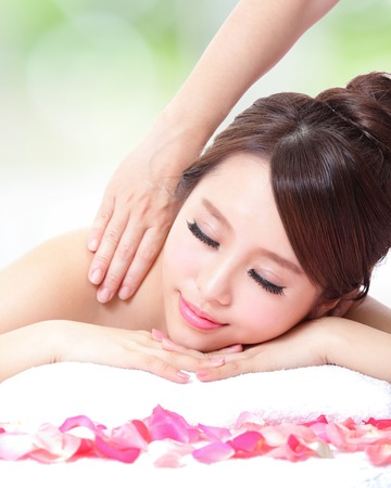 Beautiful young girl with attractive face having a massage for shoulder on resort green background, asian woman photo