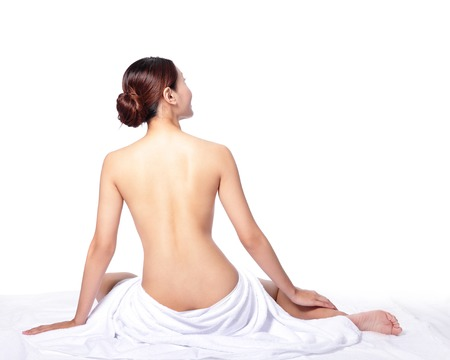woman back view and wearing towel sitting on the floor, isolated on white, asian photo