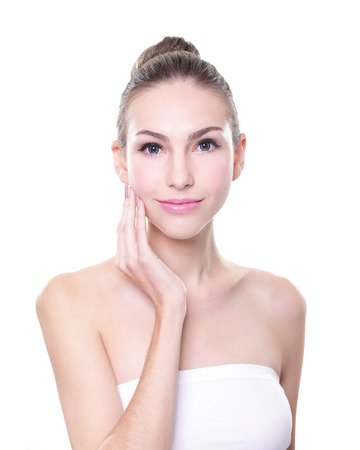 Close up portrait of beautiful young woman face and she touch her skin. Isolated on white background. Skin care or spa concept, caucasian photo