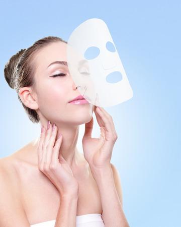 piel rostro: Relaje a la mujer joven con el pa�o m�scara facial aislada sobre fondo azul, el concepto de cuidado de la piel y la protecci�n de las quemaduras de sol, cauc�sico