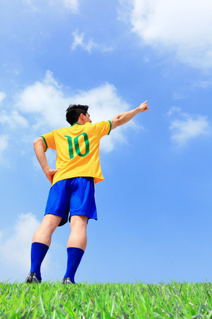 Brazil soccer player man pointing copy space at the stadium with blue sky photo
