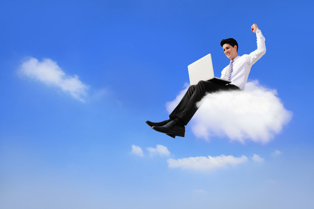 business man sitting on a cloud working with laptop, low angle view, cloud computing concept photo