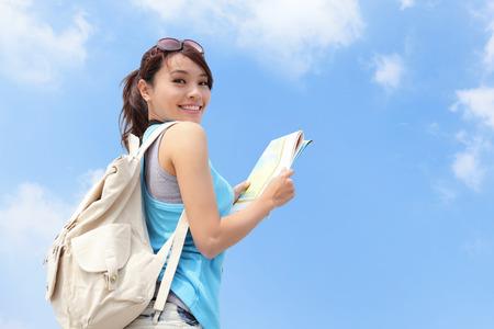 Šťastný cestování žena vypadat mapa a podívat se na vás s oblohou na pozadí, asijských