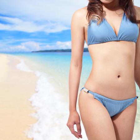 young woman in blue bikini at sea beach photo