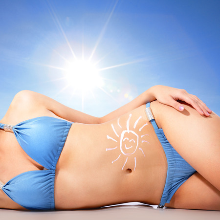 sunbath: Attractive young woman body at the beach with sun shaped cream (sun block or sunscreen lotion ) over skin