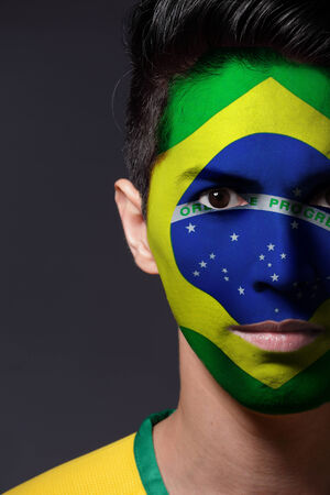 face paint: Portrait of a man with a painted flag of Brazil - Latin America