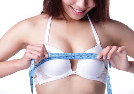 senos: mujer joven que controla su medici�n de mama aislados sobre fondo blanco, asi�tico Foto de archivo