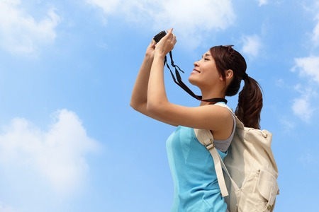 Happy woman traveler photo by camera with blue sky photo