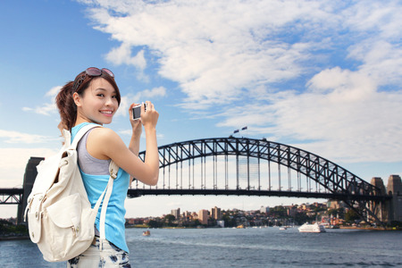 traveller: Happy woman traveler photo by camera in Australia