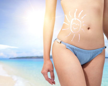 Attractive young woman body at the beach with sun shaped cream (sun block or sunscreen lotion ) over skin Stock Photo - 27342984