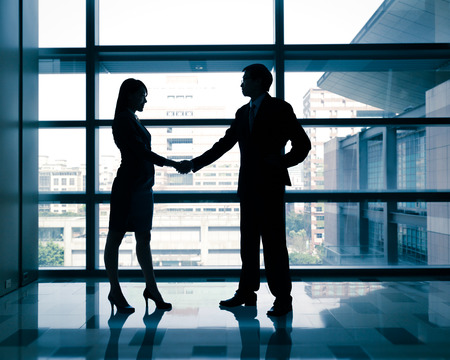 successful business woman and man handshaking with office building