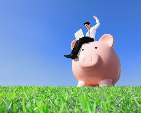 Happy Saving Money with my piggy bank - Young business man sitting on piggy bank with computer Stock Photo