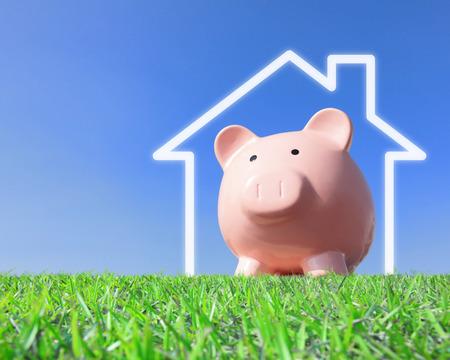 Een roze spaarvarken met nieuwe huis verbeelding visie met blauwe hemel Stockfoto