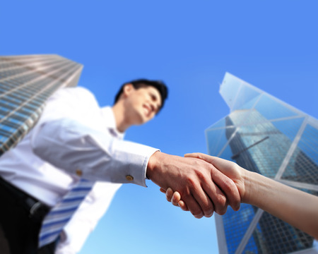 business people shaking hands with city background (focus on hand), asia, hong kong photo