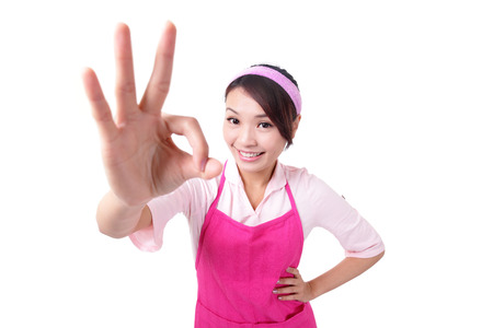 Happy young woman housewife mother wearing kitchen apron and showing OK, asian photo
