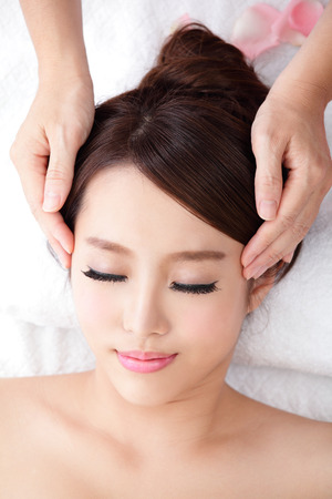 Beautiful young woman enjoy receiving face massage at spa with roses, she is very relaxed , asian beauty photo