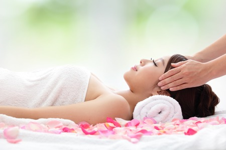 adult massage: Relax beautiful woman face receiving massage with nature green background, asian beauty