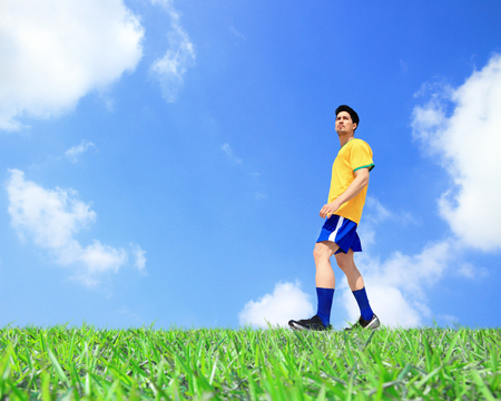 Soccer player man kick the ball at the stadium with blue sky photo