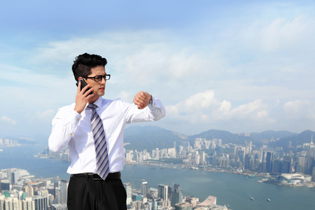 man looking at sky: business man look watch with city background, asia, hong kong