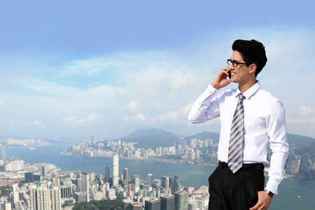 Happy business men call by smart phone on business architecture background, asia, hong kong photo