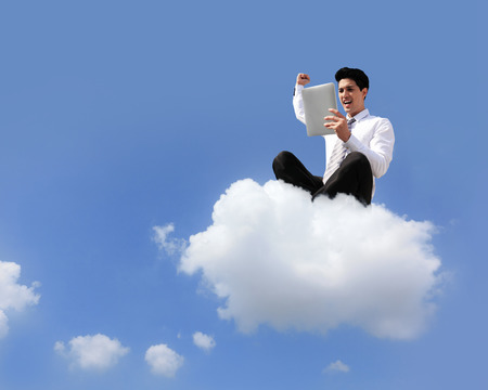 business man sitting on a cloud working with tablet pc computer..