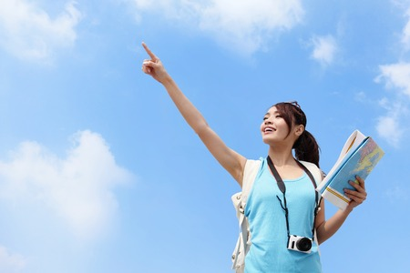 Happy women traveler pointing copy space with map in the sky photo