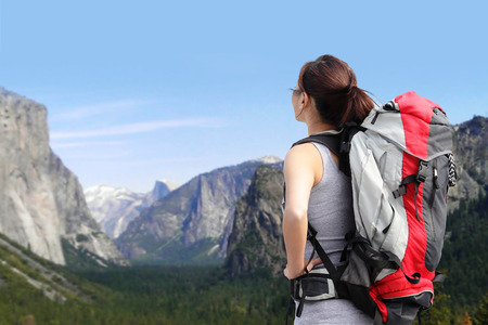 woman back view: Travel in Yosemite Park, Woman Hiker with backpack enjoying view, California, USA