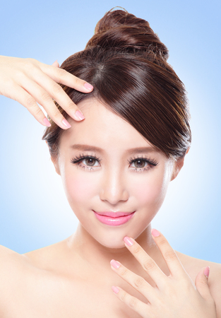 Natural health beauty of a woman face, she finger touch perfect skin with blue background, asian beauty model photo
