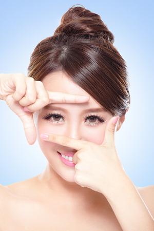 traitement: Visage de femme et des soins oculaires et elle faisant cadre avec les mains, femme asiatique Banque d'images