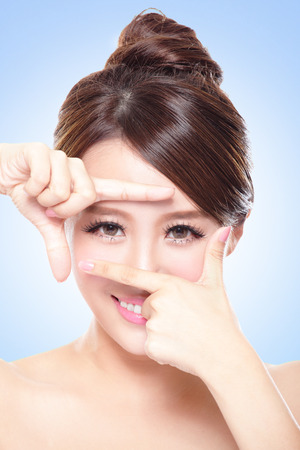 Woman face and eye care and she making frame with hands, asian woman photo