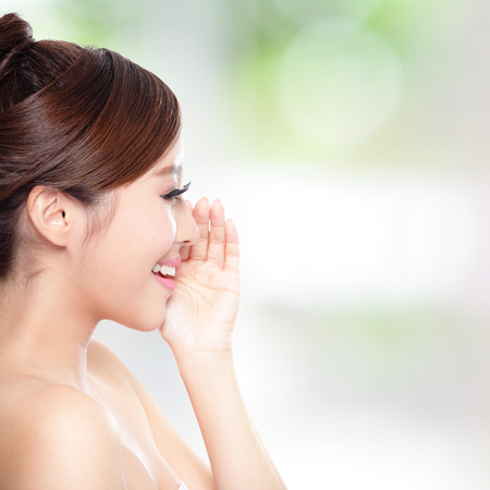 chinese woman: attractive woman with health skin and teeth, she is happy talk to you with nature green background, asian