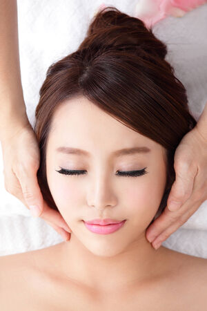 Beautiful young woman enjoy receiving face massage at spa, she is very relaxed , asian beauty photo