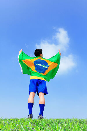 Excited man holding a brazil flag with blue sky photo