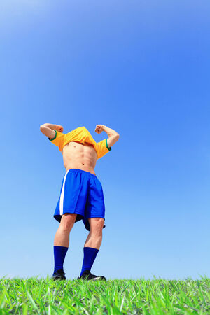 Excited Soccer player man goal at the stadium with blue sky photo