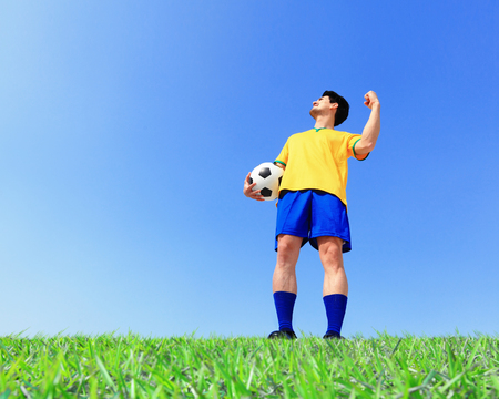 Brazilian soccer football player man holding ball at the stadium with blue sky photo