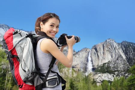 Happy woman mountain hiker taking pictures in Yosemite waterfall, California, USA, asian beauty photo