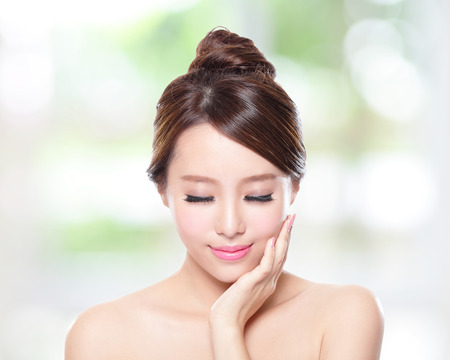 Beautiful woman smile face with clean face skin, and closed eyes , concept for eye and skin care,nature green background, asian photo