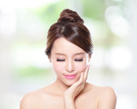 piel rostro: Cara hermosa sonrisa de la mujer con la piel limpia la cara y los ojos cerrados, concepto para el ojo y cuidado de la piel, la naturaleza de fondo verde, asi�tico