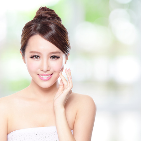 Beautiful woman smile face with clean face skin, concept for skin care, over nature green background, asian photo