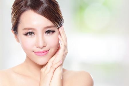 Schöne Frau, Lächeln Gesicht mit sauberen Gesicht Haut, Konzept für die Hautpflege, über die Natur grünem Hintergrund, asiatische
