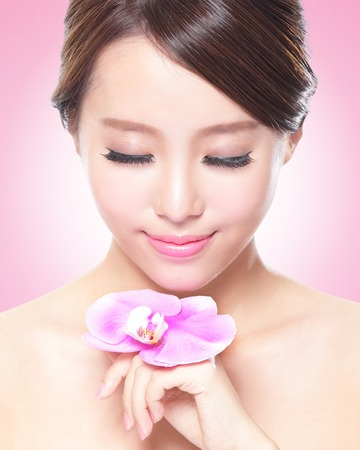 beautiful face of young adult woman with pink orchids, asian photo