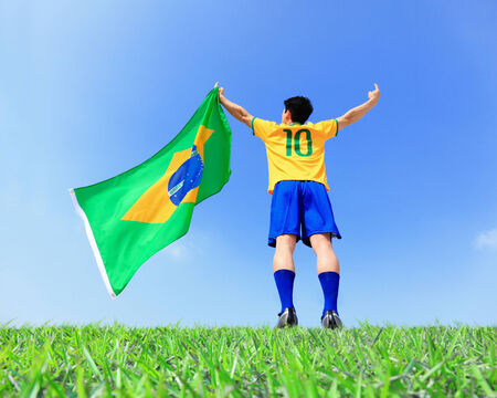 brazilian flag: Excited man holding a brazil flag with blue sky