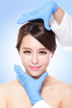 plastic surgeon: Plastic surgery touching the head of a beautiful female face