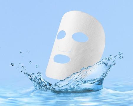 水滴付き布フェイシャルマスク、青の上に隔離 写真素材